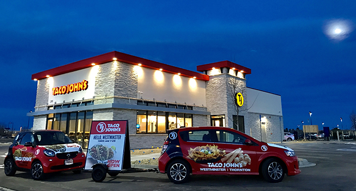Taco John's T-16 stand-alone store with two wrapped vehicles out front at night.