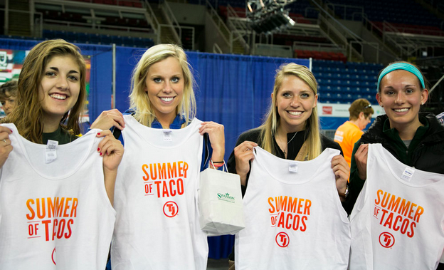 Four women holding Summer of Taco's t-shirts