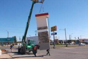 A crane lifting and carrying a part of a Taco John's store
