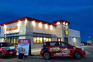An exterior of a Taco John's at dusk.