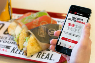 A customer holds a cell phone showing the Taco John's mobile app, set against a backdrop of a tray of food.