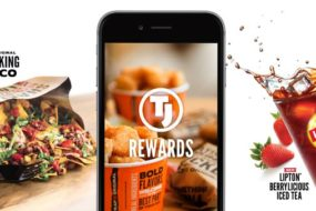A collage photo of a Walking Taco® spilling out of a foil bag onto a table, a cell phone showing a TJ® Rewards app and a glass of Lipton Berrylicious Iced Tea splashing festively over the rim of the glass with a couple of strawberries in the background.