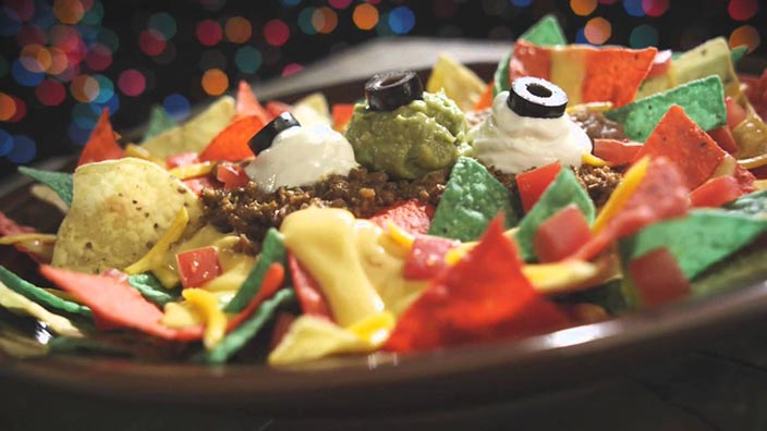 A platter of red, green and regular tortilla chips is piled high with ground beef, peppers, cheese sauce, sour cream and olives.