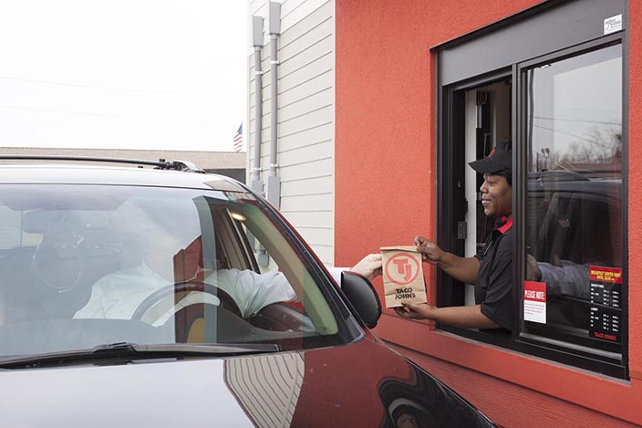 A Taco John's employee hands a bag of food to a customer in the drive-thru.