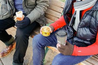 Two young men in winter wear, heads not in the photo, sit on a bench. One holds a partially wrapped burrito while the other holds Potato Olés® and a hot coffee with lid.