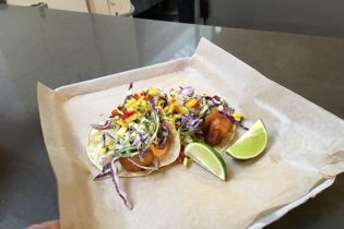 Two soft tacos displayed with lime wedges on a piece of parchment paper.