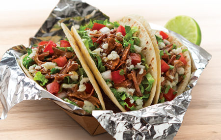 A trio of tacos rest in a tinfoil-lined cardboard tray, a slice of lime visible in the background on the right.
