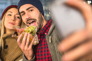 A bearded guy in a plaid shirt and wool beanie takes a selfie of himself and his girlfriend while he holds a taco in his other hand.
