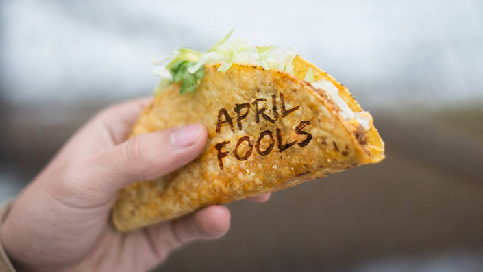 """A hand holding a taco shows what appears to be a taco shell with writing toasted on it that reads """"April Fools."""""""