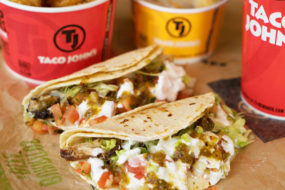Two soft-shelled fish tacos are resting on a smoothed-out wrapper with Taco John's branded cups and containers in the background.