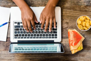 An overhead shot of two hands on a laptop keyboard, with a blue pen resting on a notebook paper on the left and a wrapped burrito and some Potato Olés® on the right.