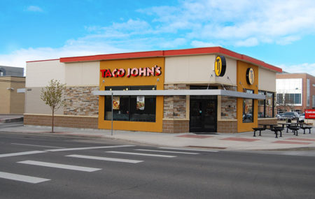 A Taco John's building is pictured on a street corner, with two picnic tables outside and a small tree growing on the sidewalk on the side of the building.