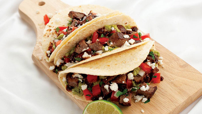 Three Sirloin Steak Tacos topped with crumbled queso fresco cheese are lined up on a wooden cutting board with a cut lime featured in the foreground.
