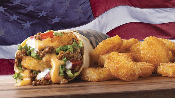 A burrito filled with ground beef, cheese sauce, lettuce, tomato and Potato Olés®, alongside more Potato Olés®, are shown against the backdrop of an American flag.