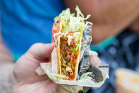A hand holds a taco in an open Taco John's wrapper, filled with lettuce, tomatoes and ground beef. An out-of-focus container of cheese dip can be seen in the background against a blue shirt.