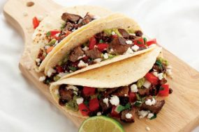 Three soft-shelled steak tacos are displayed on a wooden cutting board with a wedge of lime in the foreground.