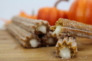 A Pumpkin Churro is stacked crosswise on top of another Pumpkin Churro, with a bit of cream oozing out of each one. A stack of three Pumpkin Churros can be seen in the background, with flecks of sugar on the wooden table top.