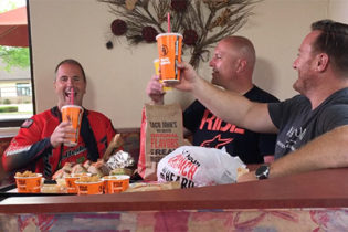 Three smiling men sit in a booth surrounded by bags of Taco John's food as well as trays of Potato Olés® on the table. The two men on the right are raising their drink cups in a toast.