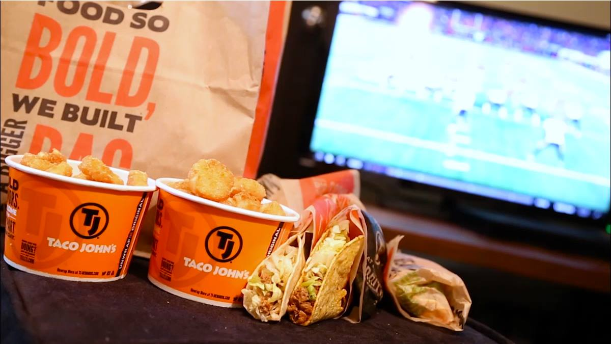A bag of Taco John's food is fronted by two cups of Potato Olés®, two tacos with ground beef and shredded lettuce, and a burrito still wrapped in paper. A football game can be seen on a TV screen in the background.