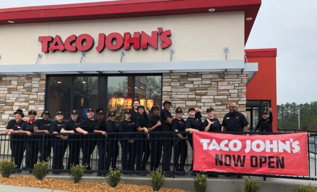 "Uniformed Taco John's employees stand outside a Taco John's building in front of a ""Taco John's Now Open"" banner on a sidewalk railing."
