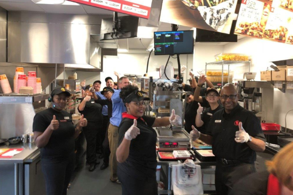 Taco John's team members hold a thumbs up to the camera while smiling as they prep food in a restaurant kitchen.